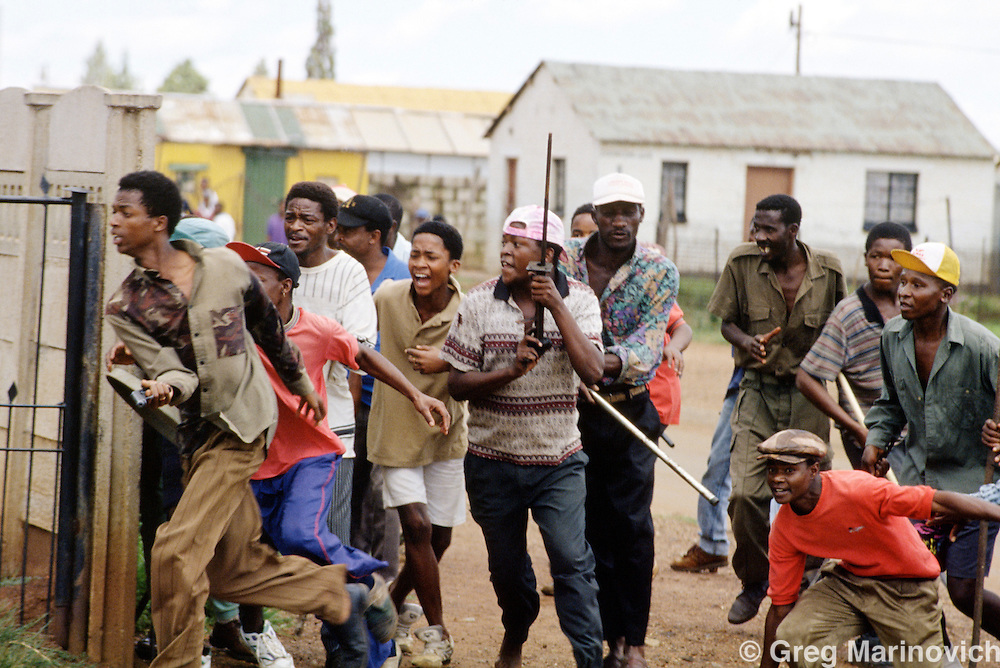Bekkersdal, Transvaal, South Africa 1994. Azapo supporters charge at ANC supporters in clashes between police, army, Azapo and the ANC is Bekkersdal township, 1994.