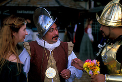 Stock photo of a man with flowers talks to a couple at the Texas Renaissance Festival in Plantersville Texas