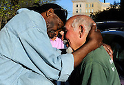 Client Michael Johnson of Hartford hugs friend Anthony Cymerys, known as Joe the barber in Hartford, Conn., Wednesday, May 1, 2013.