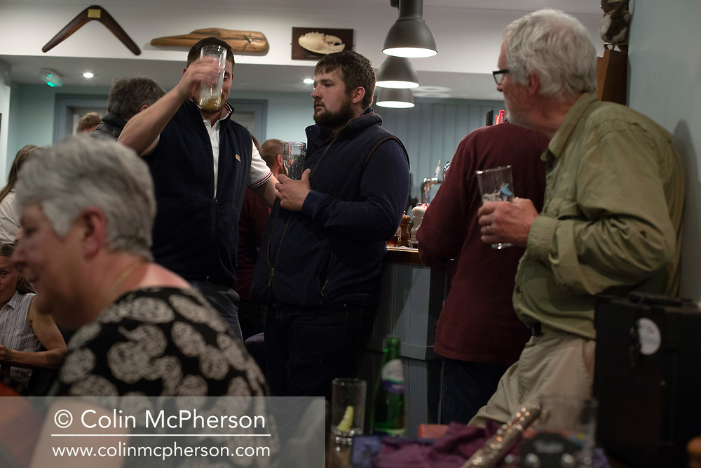 People during a music session at the Colonsay Hotel on the the Inner Hebridean island of Colonsay on Scotland's west coast.  The island is in the council area of Argyll and Bute and has an area of 4,074 hectares (15.7 sq mi). Aligned on a south-west to north-east axis, it measures 8 miles (13 km) in length and reaches 3 miles (4.8 km) at its widest point, in 2019 it had a permanent population of 136 adults and children.
