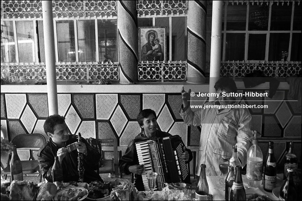 TWO MUSICIANS PLAY MUSIC AS PART OF THE MIHAI FAMILYS' ROMANIAN ORTHODOX EASTER CELEBRATIONS. LIULIU GOGU MIHAI DANCES IN THE PYJAMAS HE HAS BEEN GIVEN AS A PRESENT BY A GOD-CHILD. SINTESTI, ROMANIA, MAY 1997..©JEREMY SUTTON-HIBBERT 2000..TEL./FAX. +44-141-649-2912..TEL. +44-7831-138817.