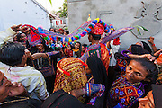 The family of the groom perfoming a ritual when the bride and the groom dressed in colorful clothes enters the home after getting married.
