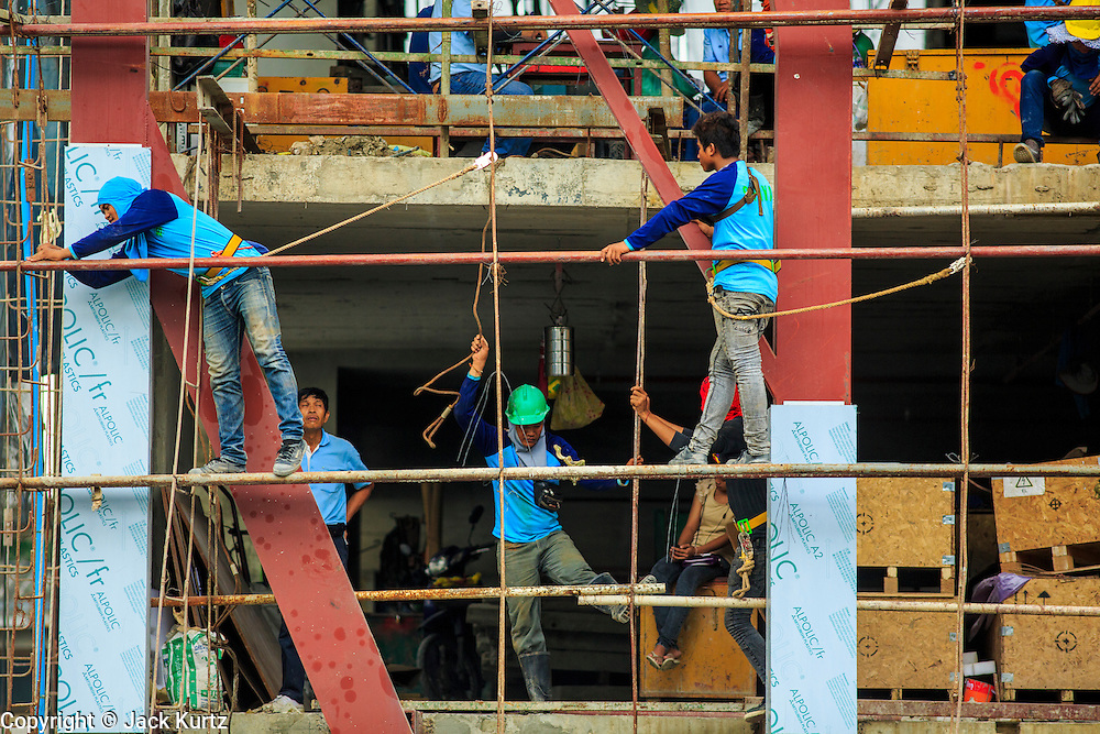 16 OCTOBER 2012 - BANGKOK, THAILAND: Construction workers on scaffolding at a residential condominium project on Th Phaya Thai near the intersection with Phetchaburi Rd. in Bangkok. The global economic slowdown had little visible effect in Bangkok. Construction projects dot the city of 12 million and development continues unabated.    PHOTO BY JACK KURTZ