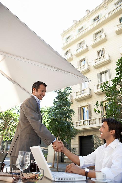 Businessmen shaking hands at outdoor cafe