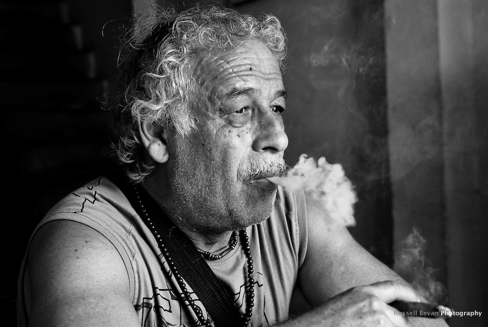 A fellow traveller poses for a portrait while smoking a cigar in Varanasi, Uttar Pradesh, India