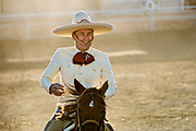 Juan Franco smiles after successfully downing a steer rides during the Colas en el Lienzo event at the family Charreria practice session in the Jalisco Highlands town of Capilla de Guadalupe, Mexico. Colas en el Lienzo or Steer Tailing is similar to bull dogging except that the rider does not dismount; the charro rides alongside the left side of the bull, wraps its tail around his right leg, and tries to bring the bull down in a roll as he rides past it.