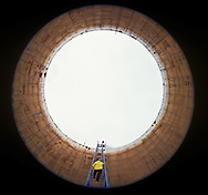 Refinery worker inspecting interior of oil storage tank, Purvis, Miss.