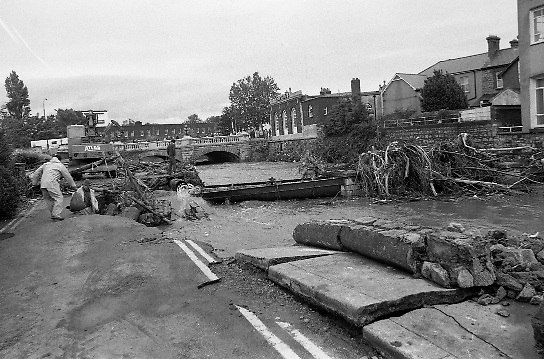 "Flooding at the Dodder..1986..28.08.1986..08.26.1986..28th August 1986..As a result of Hurricane Charly (Charlie) heavy overnight rainfall was the cause of severe flooding in the Donnybrook/Ballsbridge areas of Dublin. In a period of just 12 hours it was stated that 8 inches of rain had fallen. The Dodder,long regarded as a ""Flashy"" river, burst its banks and caused great hardship to families in the 300 or so homes which were flooded. Council workers and the Fire Brigades did their best to try and alleviate some of the problems by removing debris and pumping out some of the homes affected..Note: ""Flashy"" is a term given to a river which is prone to flooding as a result of heavy or sustained rainfall...Picture shows work men at the site where the road had subsided near the bridge over the Dodder at Ballsbridge, Dublin.The picture also shows damage to a water main and the amount of debris carried down river by the flood"
