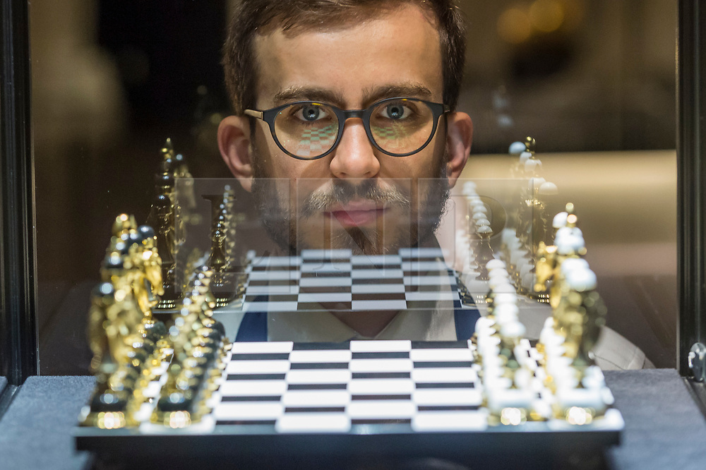 "© Licensed to London News Pictures. 25/10/2019. LONDON, UK. A technician poses next to ""a modern gilt-brass hardstone chess set"" (Est. GBP6-8k).  Preview of ""GOLD: The Midas Touch"" at Sotheby's in New Bond Street.  Artworks spanning six centuries dedicated to gold will be offered for sale on 29 October.  Photo credit: Stephen Chung/LNP"