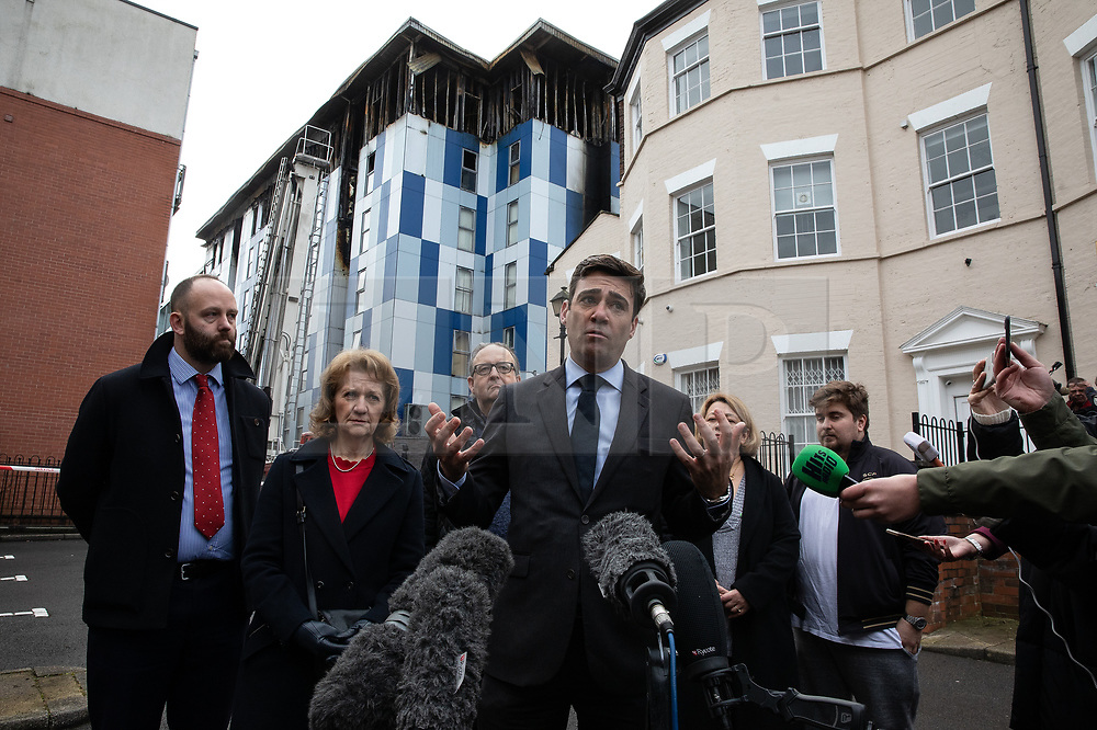 """© Licensed to London News Pictures. 16/11/2019. Bolton, UK. PAUL DENNETT of Greater Manchester's High Rise Taskforce , Deputy Mayor of Greater Manchester BEV HUGHES , DAVID GREENHALGH of Bolton Council , Mayor of Bolton Mayor of Manchester ANDY BURNHAM and SANDRA RUIZ and TIAGO ALVES of Grenfell United, both of whom are former Grenfell Tower residents , at a press conference at the site of the blaze . Firefighters work at the scene where a fire broke out overnight (15th/16th November 2019) at a block of flats known as """" The Cube """" , in Bolton Town Centre . At least two people are known to have been treated by paramedics at the scene of the six-story block , which is occupied by students of the University of Bolton . Photo credit: Joel Goodman/LNP"""