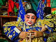 17 OCTOBER 2018 - BANGKOK, THAILAND: A man gets help getting into his costume before the Chinese opera on the last night of the Vegetarian Festival at Chit Sia Ma Shrine in Bangkok's Chinatown. The Vegetarian Festival, also called the Nine Emperor Gods Festival, is a nine-day Taoist celebration beginning on the eve of 9th lunar month of the Chinese calendar. Traditional Chinese operas, called Ngiew in Thailand, are sponsored at many Chinese shrines and temples during the Vegetarian Festival.    PHOTO BY JACK KURTZ