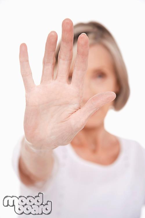 Senior woman holding up palm of hand studio shot
