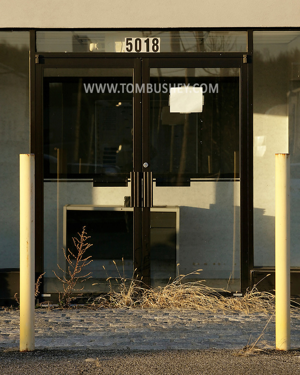 New Hampton, New York - Weeds grow in front of the door of a vacant building, formerly a car dealership, on March 19, 2011.