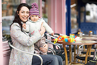 Mother holding baby on lap sitting in outdoor cafe