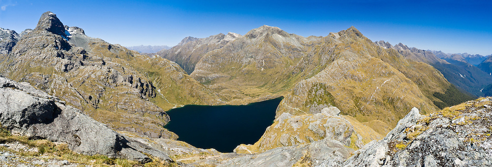 The Routeburn Track cuts through the pass of Harris Saddle at the base of Ocean Peak (right, 1848 meters) to forested Hollyford Valley in Fiordland National Park on the right. The view from Conical Hill includes Mount Xenicus (left, 1912 meters elevation) and Harris Lake in Mount Aspiring National Park in the Southern Alps, South Island, New Zealand. Panorama stitched from 5 overlapping photos.