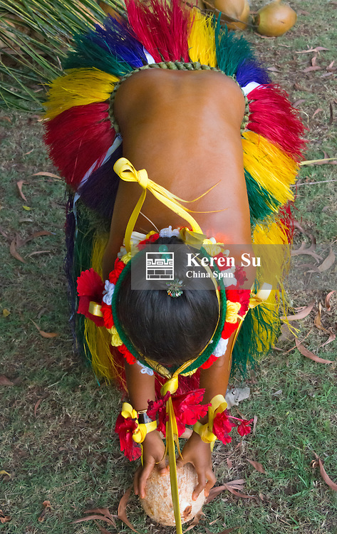 Yapese girl in traditional clothing picking up coconut at Yap Day Festival, Yap Island, Federated States of Micronesia
