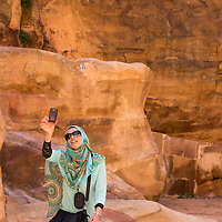 Jordan, Petra, Young Arab woman takes snapshots with mobile phone beneath stone cliffs at ancient ruins