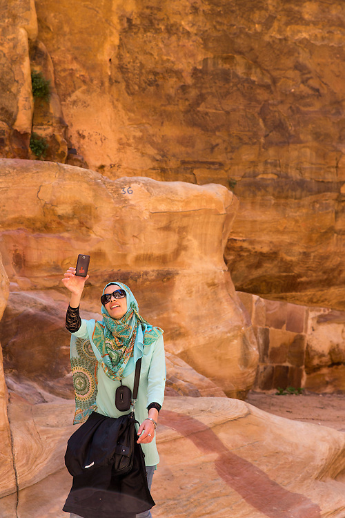 Jordan, Petra, Young Arab woman takes snapshots with mobile phone beneath stone cliffs at ancient ruins