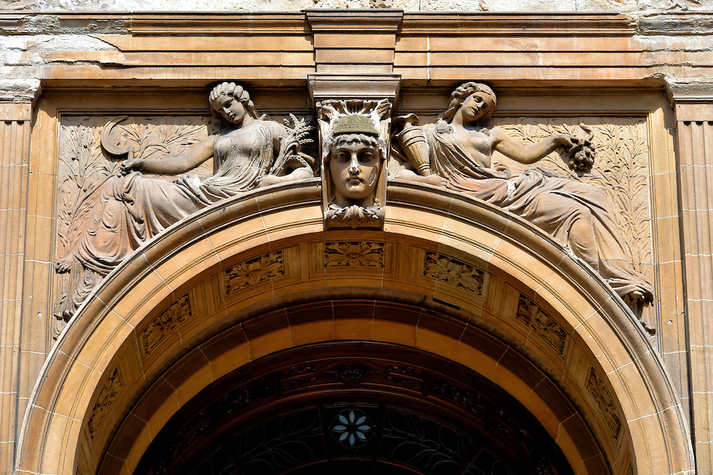 James Sellars House Allegories in Glasgow, Scotland<br /> This sandstone building was the New Club when it was built in 1879.  In 1981, it was renamed the James Sellars House in honor of its architect. Sellars became a prolific architect in Glasgow after his career was launched for designing St Andrew&rsquo;s Halls. In 1888, he died of blood poisoning at the age of 45 after stepping on a rusty nail during construction of the Glasgow International Exhibition.  These allegories over the arched entrance were sculpted by William Mossman II. This is now an office building named after its address at 144 West George Street.