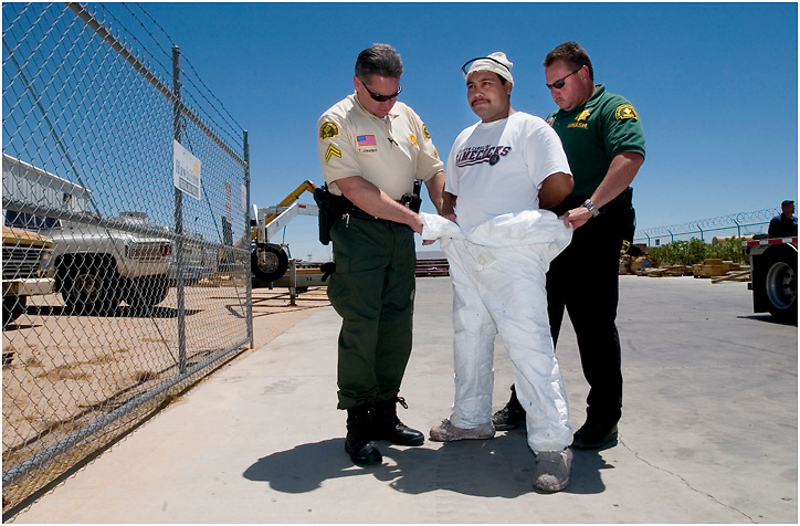 Michael Stenerson / Staff Photographer.Detective Tim Jimerson, left, and deputy Mark James arrest a man at his job during a search warrant sweep in Adelanto on Thursday. The man's identity could not be confirmed due to his use of several fake names and social security numbers.