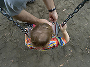 Father closing safety chain of seat with child on a swing
