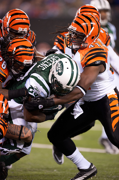 EAST RUTHERFORD, NJ - NOVEMBER 25: Shonn Greene #23 of the New York Jets rushes during the game is tackled by Chinedum Ndukwe #41 of the Cincinnati Bengals  on November 25, 2010 at the New Meadowlands Stadium in East Rutherford, New Jersey.The Jets defeated the Bengals 26 to 10. (Photo by Rob Tringali) *** Local Caption *** Shonn Greene;Chinedum Ndukwe