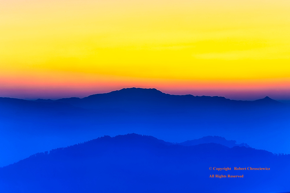 Yellow Over Blue: Mornings surprisingly deep, clear, yellow sky is in stark contrast over the blue, fog covered foothills of Darjeeling India.