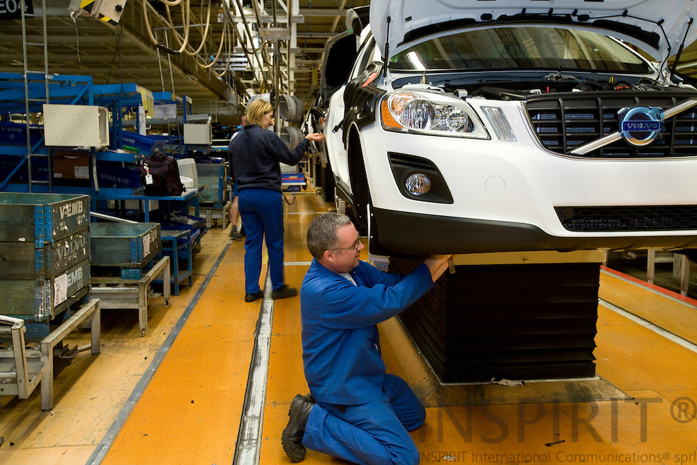 GHENT - BELGIUM - 13 NOVEMBER 2008 -- Volvo Cars Gent -- A worker fits plastic protection for the brakes on a Volvo car at the assembly line.  Photo: Erik Luntang/INSPIRIT Photo