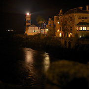 The lighthouse and Mansion at Santa Marta at night in the swank part of Cascais/Estoril on the Atlantic at night, with a container ship in the distance heading into Lisbon