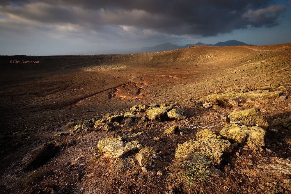 Approaching weather front over the southern volcanic peaks of Lanzarote seen from the Montaña Roja crater in Playa Blanca. The stones were covered in Lichens giving them a white/green colour against the red earth below.