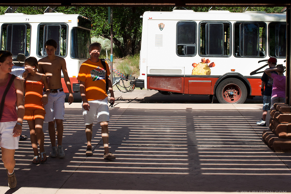 Tourists exit the Zion shuttle system at the visitor's center at Zion National Park in Utah.