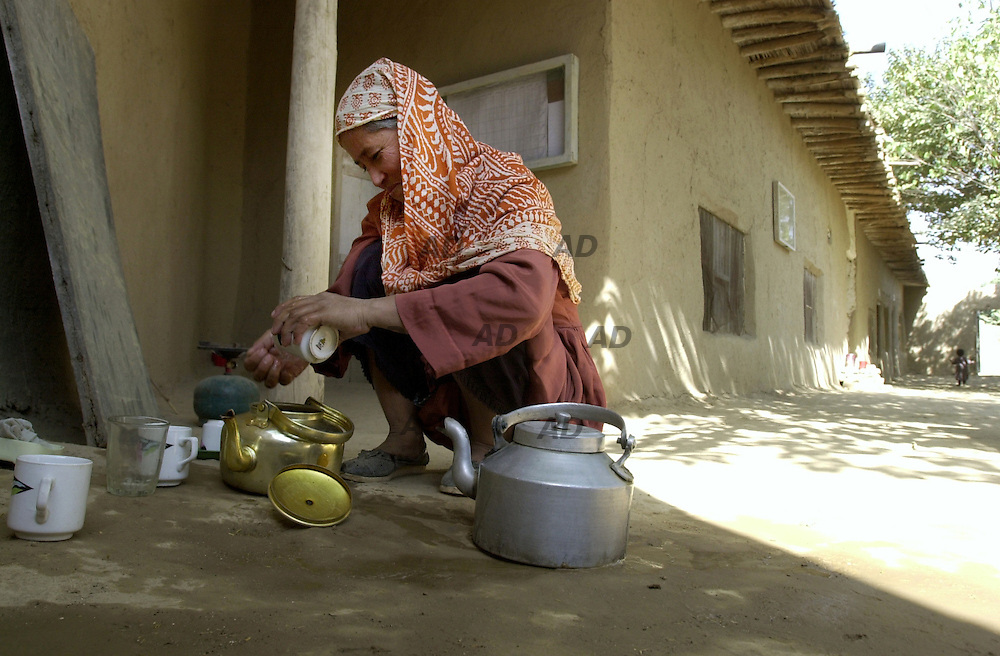 RAWA (Revolutionary Association of the Woman of Asghanistan) activities in Khewa Camp. A woman washing the teapot.
