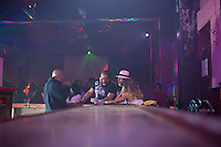 Three tourists from Greece talk with a bartender at 1:30 a.m. in Havana, Cuba