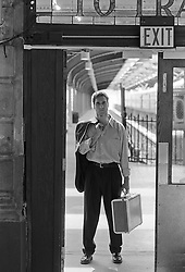 man holding a suitcase at a train station in New Jersey