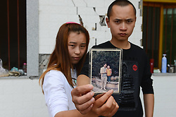 59601368 .The 23-year-old Luo Yunchao (R) and his 20-year-old girlfriend Li Yanyan pose for photo with an old picture in the quake-hit Longmen Village, southwest China s Sichuan Province, May 4, 2013. The old picture of Luo and his brother was taken in 1997 when he was 7 years old. Old photos are not daily necessities for who just suffered a 7-magnitude earthquake, but they are still cherished as they recorded peoples past life and recalled memories, May 4, 2013.  Photo by: i-Images.UK ONLY