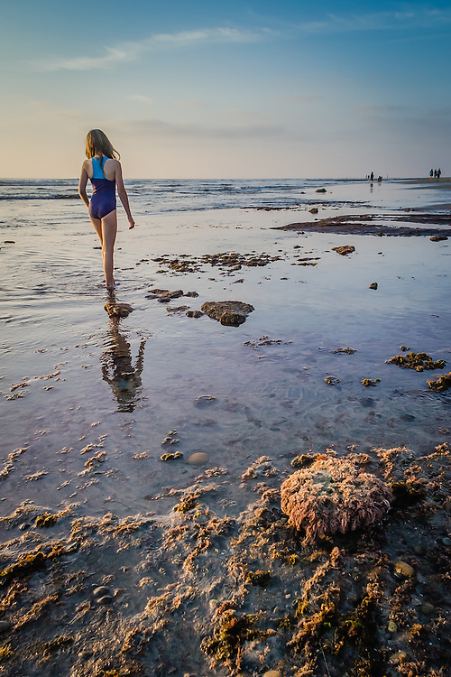 Photo of a girl walking through the tide pools at sunset on Swami's in Encinitas, California