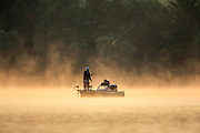 Two anglers fish on a northern Wisconsin lake in the early morning mist.