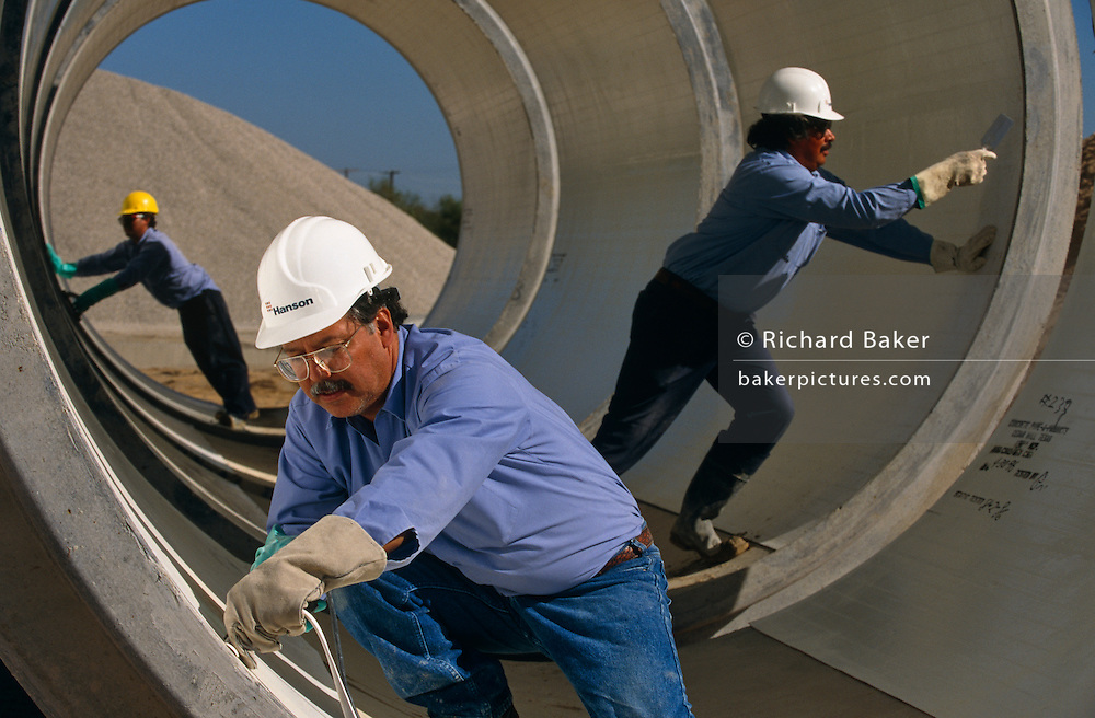 """Precast concrete pipes are prepared for distribution by a Mexican-born employees at Hanson Pipe & Products, Grand Prairie, Texas, USA. They are inspcting the inner-surfaces and tongue and groove seals of the horizontal pipes wearing obligatory hard hats and corporate blue shirts. Precast concrete is made from a reusable mold or """"form"""" and cured in a controlled environment, then transported to the construction site and lifted into place. Used in the construction of commercial building components, bridges, manholes and retaining walls, these products are the strongest pipe available, designed and plant tested to resist any load required with a design life of 70-100 years. ..."""