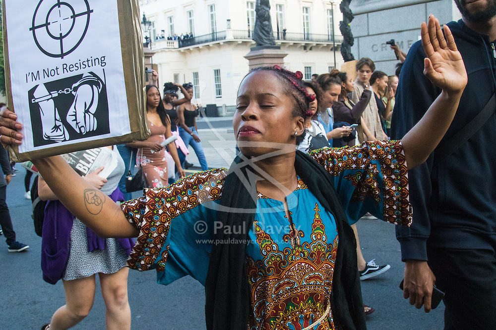 "London, July 8th 2016. Hundreds gather on London's Southbank before marching through the streets of London to Parliament Square, Downing Street and the BBC, in a Black Lives Matter protest in solidarity with Americans following the shooting dead of two black men, Philando Castile in Minnesota and Alton Sterling in Louisiana by police in the US. PICTURED: A woman marches with her hands up as the crowd chants ""Hands up! Don't shoot!""."
