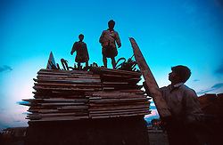 BANGLADESH CHITTAGONG MADHOM BIBIR HAT OCT00 - Labourers load doors and loose carpets onto a truck during sunset at the beach of Chittagong. Doors, furniture and bathroom fittings fetch good prices on local markets and add to the income of the ship-breaking entrepreneurs who are primarily concerned with recycling the scrap metal...Several thousand labourers work on one medium-sized (50,000 ton) ship for a period of around three months, until it is completely dismantled and taken apart. ..Since Bangladesh does not possess mineral resources such as iron ore, it works out more cost-efficient to employ a large army of day-labourers to recycle the scrapped ships rather than to import ore. On average, a labourer can expect to earn a little more than 1 US Dollar per day...jre/Photo by Jiri Rezac..© Jiri Rezac 2000..Contact: +44 (0) 7050 110 417.Mobile: +44 (0) 7801 337 683.Office: +44 (0) 20 8968 9635..Email: jiri@jirirezac.com.Web: www.jirirezac.com..© All images Jiri Rezac 2000 - All rights reserved.