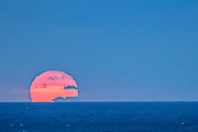 The rising sun lifts above the ocean horizon at Harbor Beach in Fort Lauderdale, Florida.