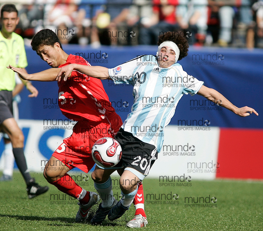 Argentina's Lautaro Acosta(R) is tripped up by North Korea's (DPRK) Nam Chol Pak during their match at the FIFA U-20 World Cup on 06 July 2007 in Ottawa, Ontario, Canada. Argentina defeated North Korea 1-0..AFP PHOTO/GEOFF ROBINS