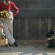 A street scene in New Delhi. A sweet potato vendor talking to a freind sitting on the ground next to his portable stall.
