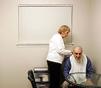 "Barbara Blum puts a bib on her husband Jack before breakfast in their suburban Atlanta, Ga. apartment on Friday morning, Feb. 17, 2006. Mrs. Blum, 77, has taken on the role of caregiver for her 88-year-old husband, whom a doctor believes has Alzheimer's disease, she said. The four to five hours of sleep she gets each night is sufficient, but the situation might be taking a toll, she said. ""I am sure I'm depressed,"" she said. ""I'm not interested in socializing."""
