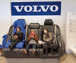 Young female visitors relaxing on over-sized seats at Volvo Museum in Gothenburg Sweden