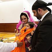 Hounslow, Greater London, UK, January 25, 2015. Sikh Temple Gurdjwara Sri Guru Singh Sobha. <br /> Ashreena is celebrated by the Priest during the ceremony. The orange scarf is meant to give the girl God's blessing and to wish her good luck in her life. Unlike what usually happens in the Indian community, where even today daughters are not celebrated, Gurmeet and her husband Sandeep, decided to give a big party for wishing a happy birthday to their daughter and blessing girls in general.