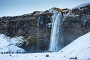 Tourists at spectacular waterfall Seljalandsfoss in South Iceland with glacial melting waters from Eyjafjahajokul icecap