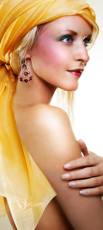 portrait of young woman in profile wearing a yellow head scarf