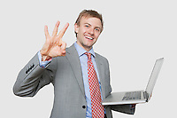 Portrait of cheerful businessman with laptop gesturing ok sign over colored background