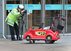 © Licensed to London News Pictures. 23/10/2015. Guilford, UK. . A child's shopping buggy is photographed by a police officer at the entrance to The Friary shopping centre after a car injured a number of pedestrians.  Photo credit: Peter Macdiarmid/LNP